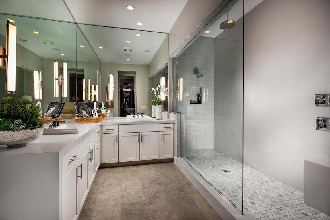 Luxury bathroom with wraparound vanity and walk-in shower.