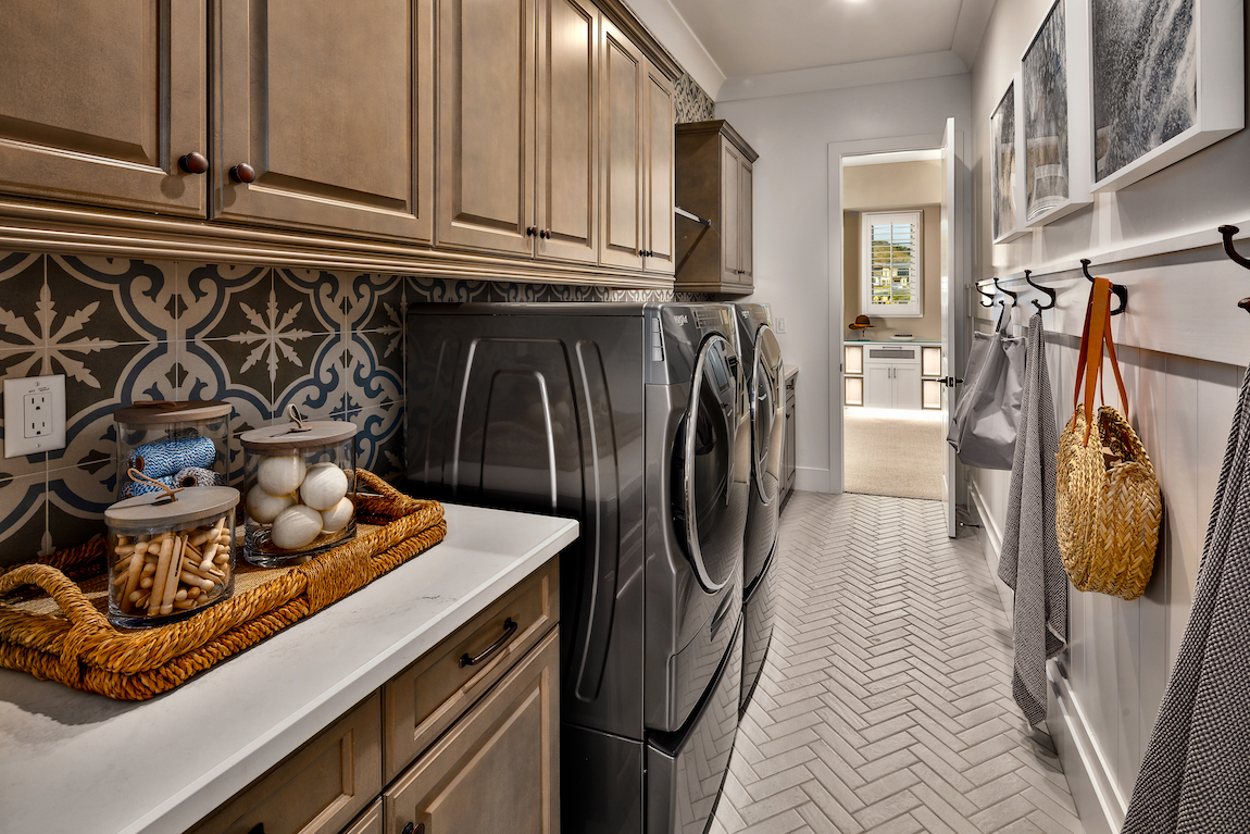 Laundry room with backsplash and brown cabinets