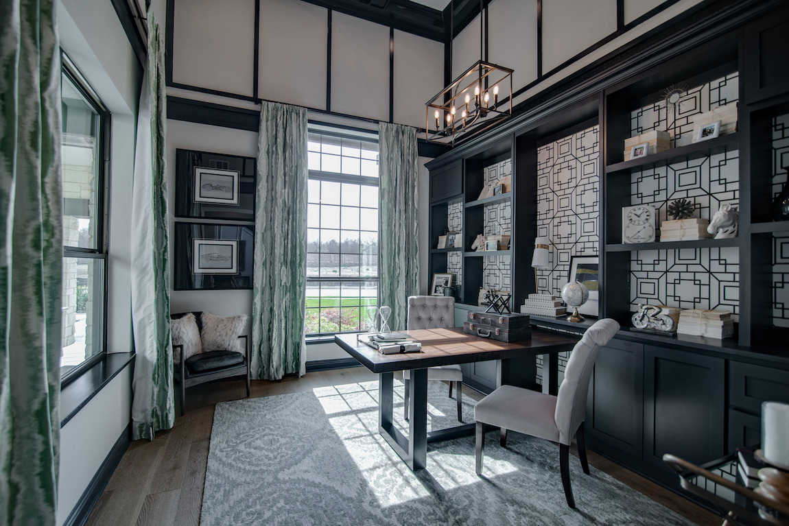 Luxurious home office design with a tall ceiling and shelves for storage.