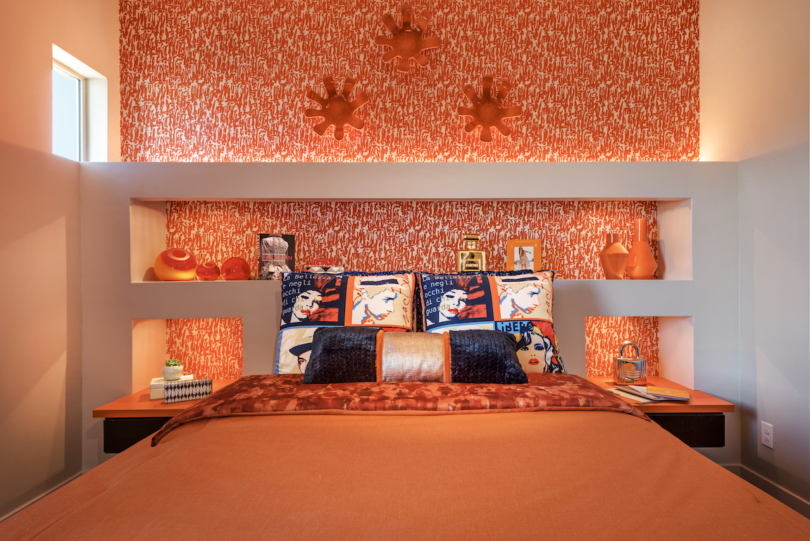 Orange bed sheets and wallpaper with pop art pillows