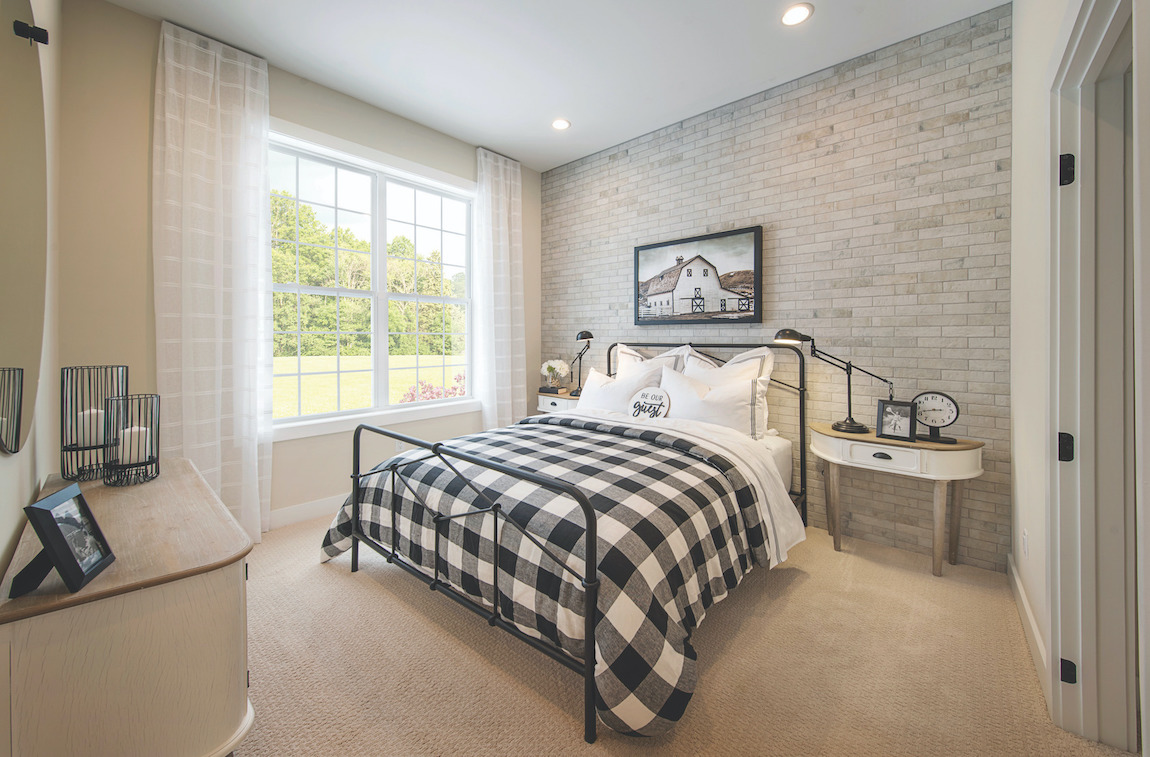 Bedroom with a bed and iron frame and brick wall.