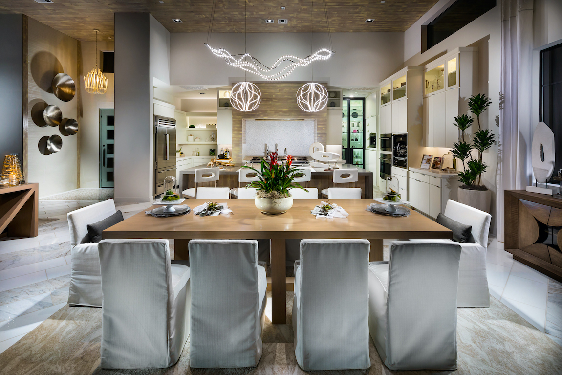 Covered dining chairs with silver light fixtures and wooden table in kitchen