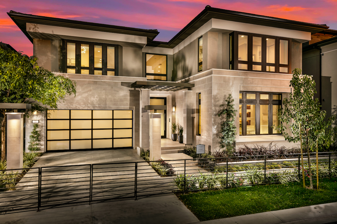 Tan exterior home with intricate window frames and iron gate, located in California.