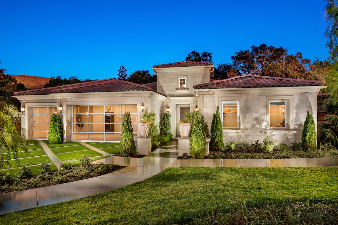 One-story luxury home with intricate landscaping and pathway to door.