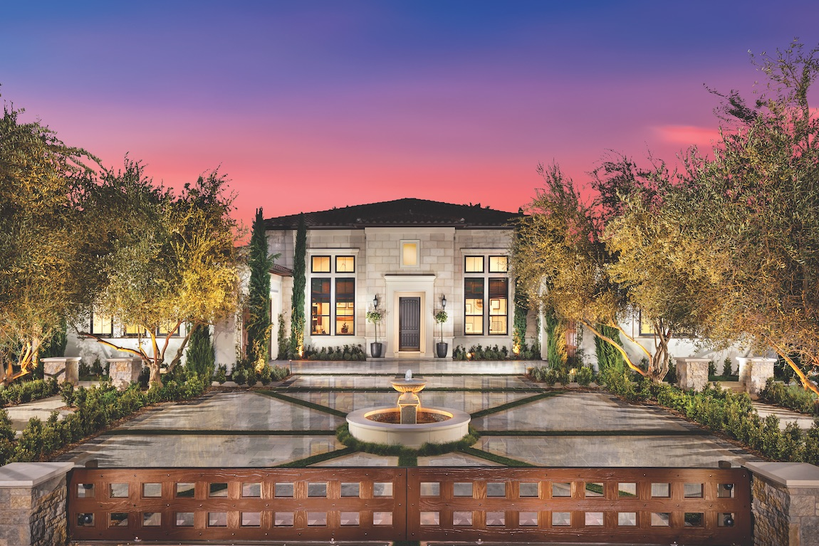 Home exterior with rounded water fountain and elaborate driveway.