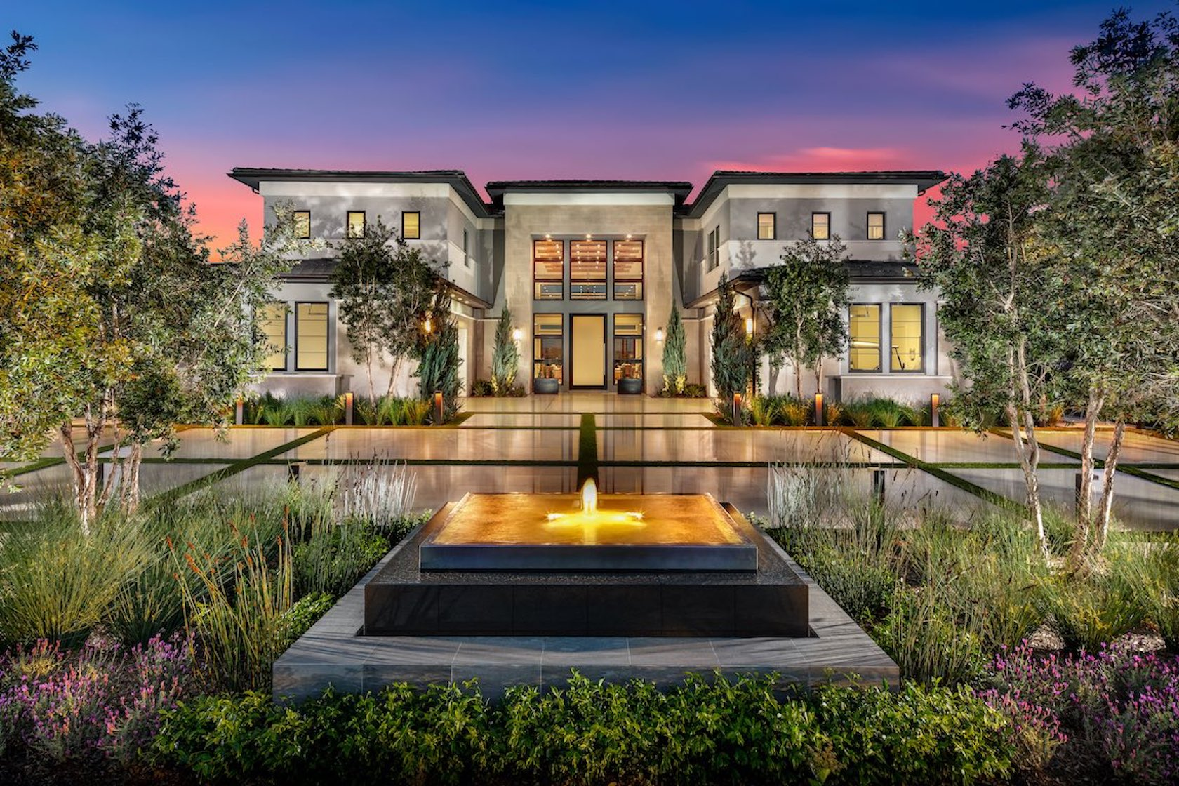 Exterior of luxury home with water fountain.