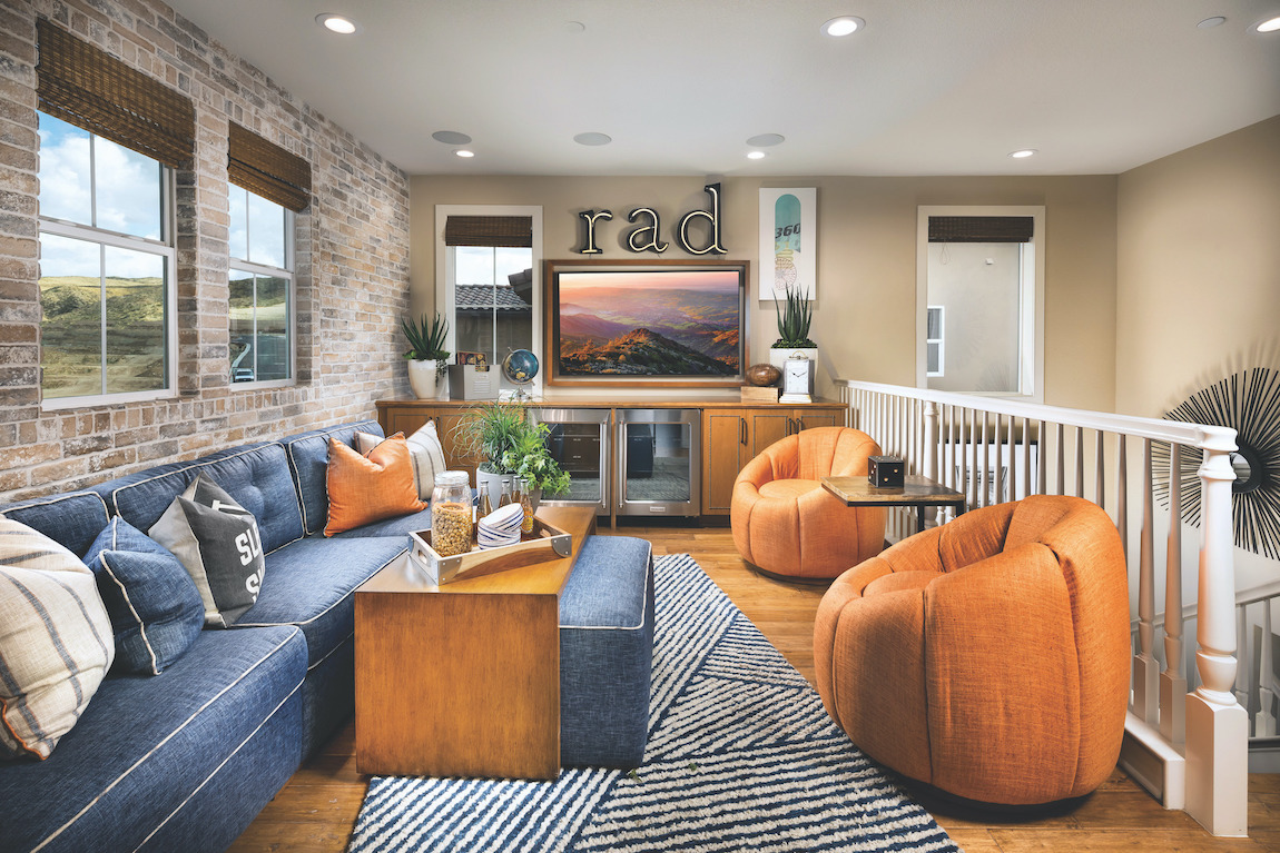 Game loft with stone wall accent with blue couch and orange chairs.