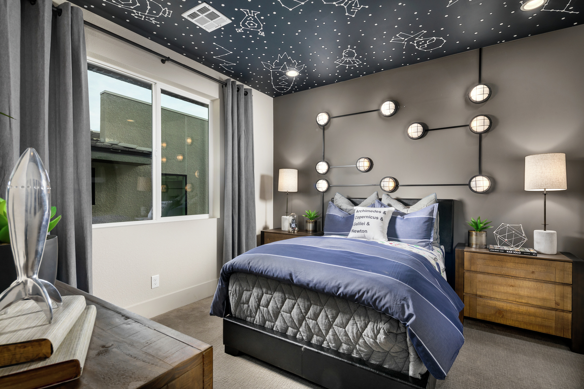 Space themed bedroom with purple comforter, starry night sky ceiling wallpaper and globe accent light fixtures on wall