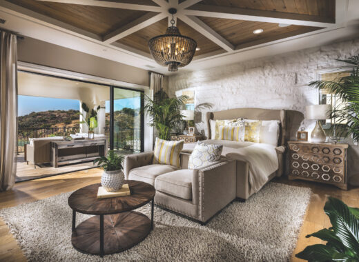 Bedroom with stone wall accent and beamed ceilings