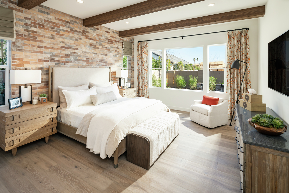 Monochromatic bedroom with brick accent, wooden beams and rustic design