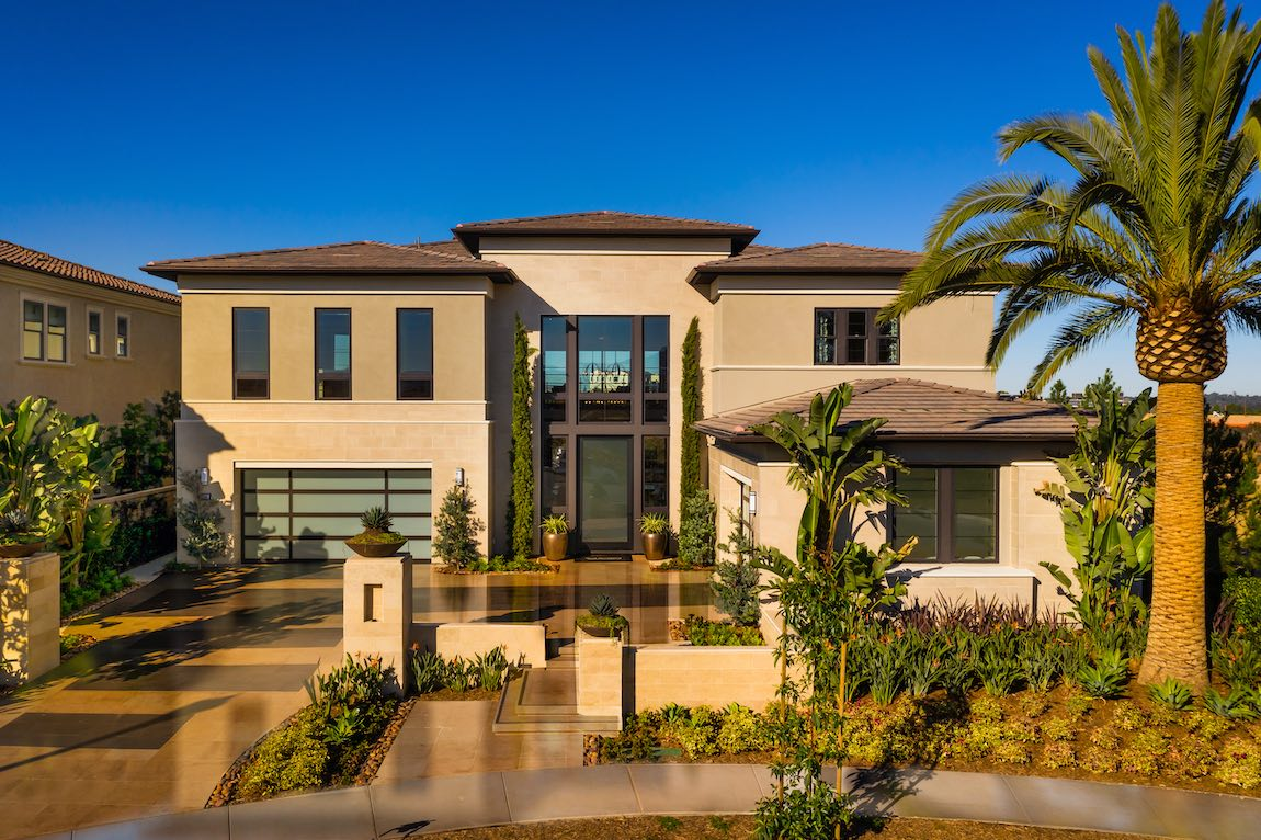 Large home with sizable glass windows planking the main entranceway.