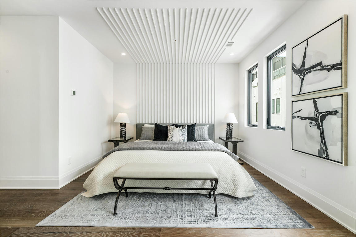 White bedroom design with panel wood accents as headboard with white and black color scheme