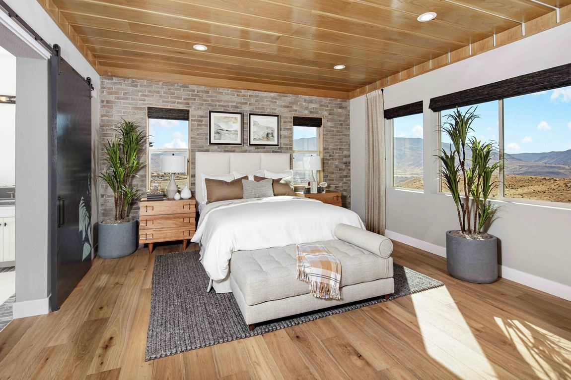 Warm brick accent bedroom design with recessed lighting and wood paneled ceiling