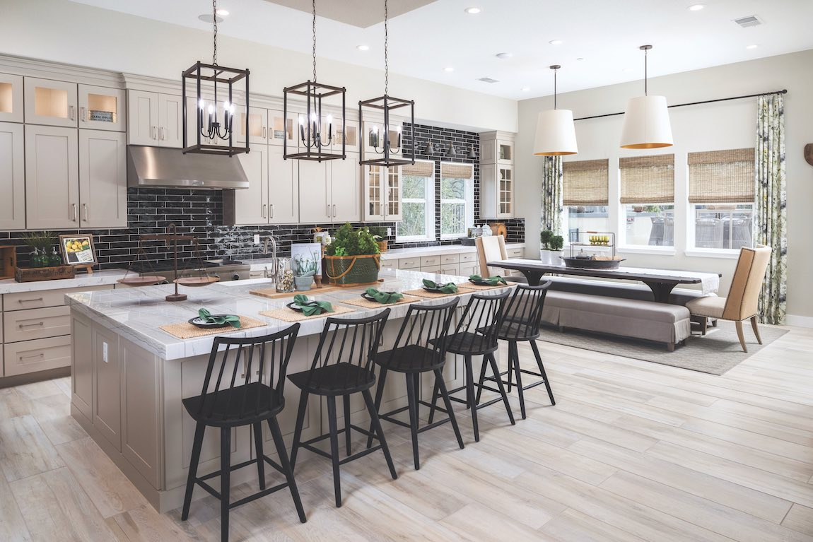 Modern farmhouse kitchen with a long breakfast nook table with benches for seating.