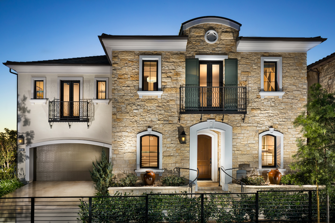 Home with light stone exterior and evenly spaced windows with iron balcony.