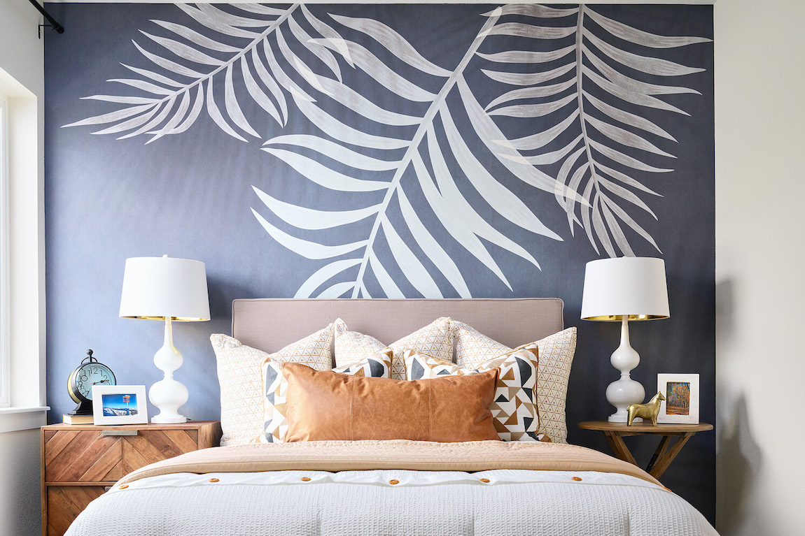 Bedroom with tropical leaf mural wallpaper with brown leather pillow and bed lamps