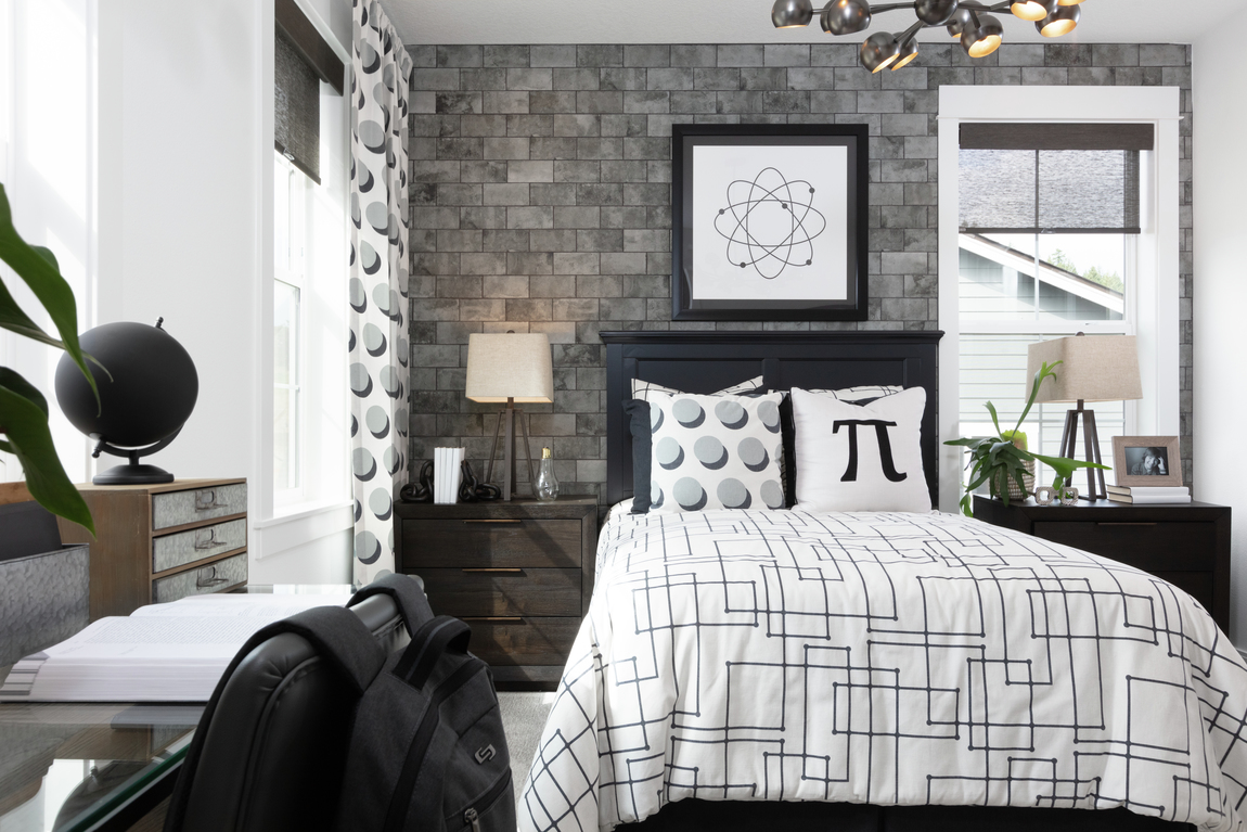 Modern bedroom design with industrial lighting fixture and brick accent wall
