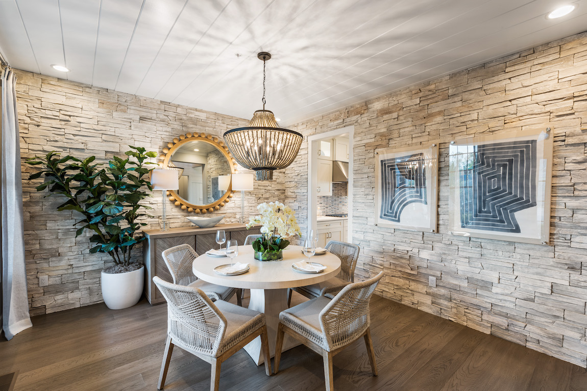 Dining room with coastal design and stone accent wall