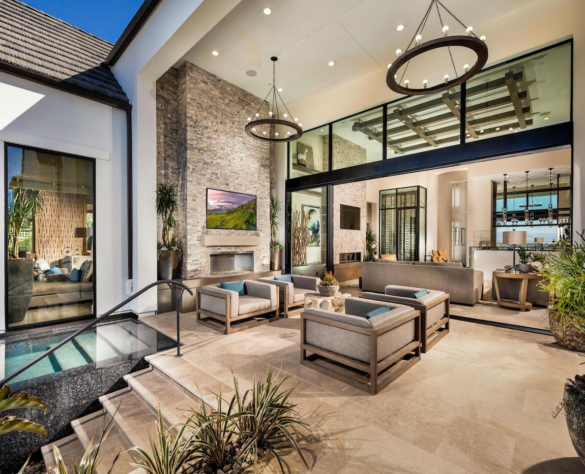 Luxurious indoor/outdoor living area with a fire pit and TV.