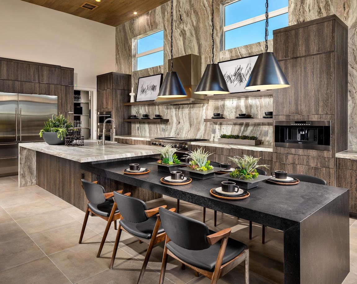 A modern kitchen featuring natural elements such as marble islands, decorative plants, and stone tiles.
