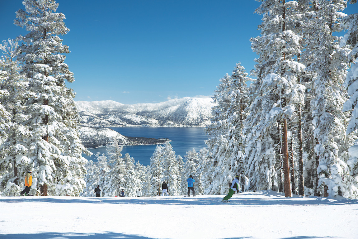 Skiers in slope on top of beautiful mountain with lake view