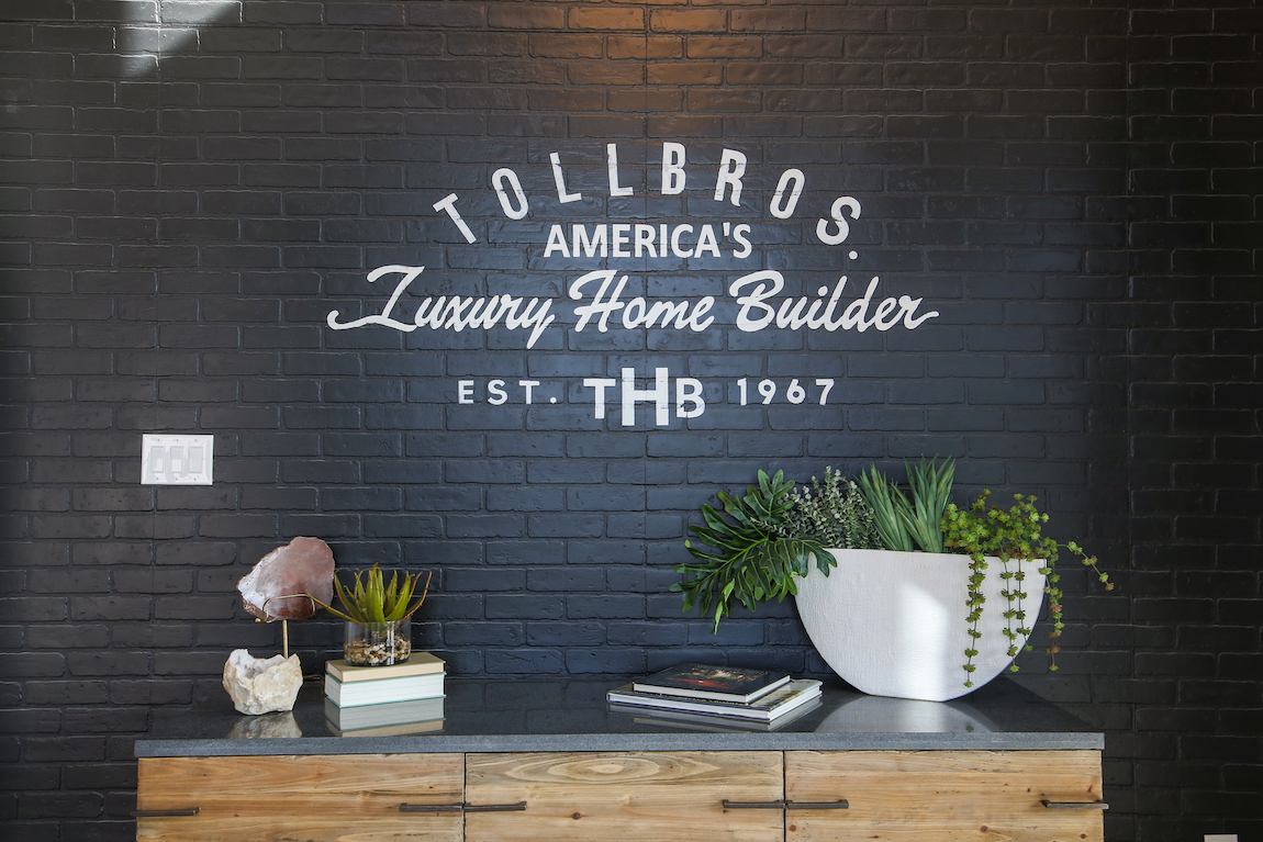 "Black brick wall with text ""Toll Brothers America's Luxury Home Builder."""