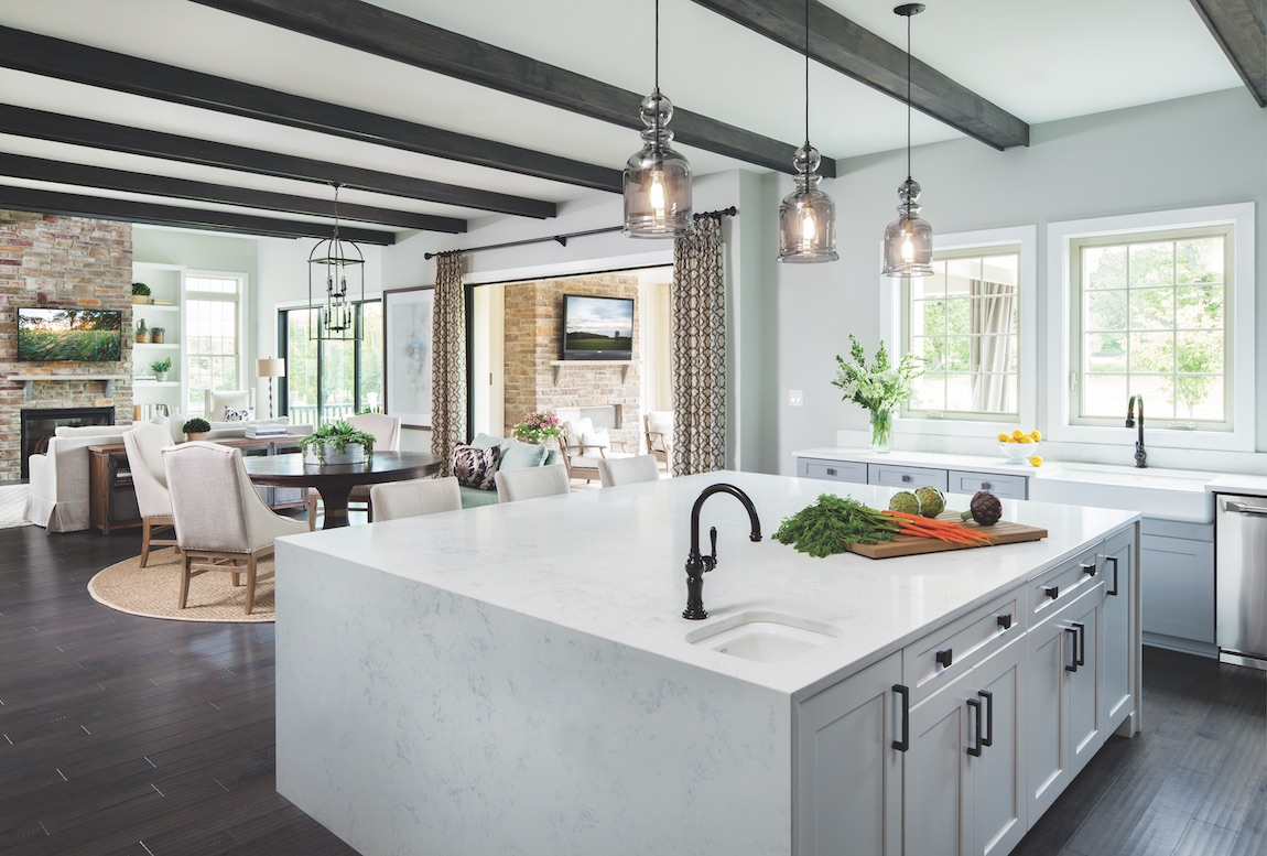 Open floor plan and kitchen with quartz waterfall countertop and black beamed ceiling.