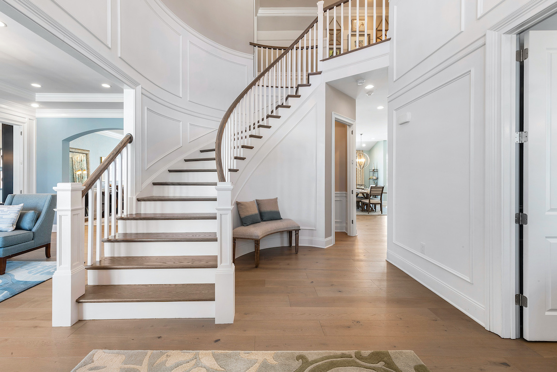 Grand staircase with curve and hard wood floors