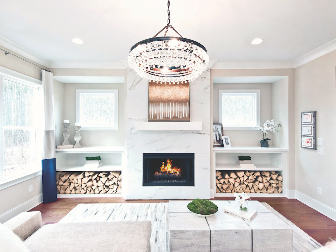 Luxury great room with accent wall, built-in shelving, and striking chandelier