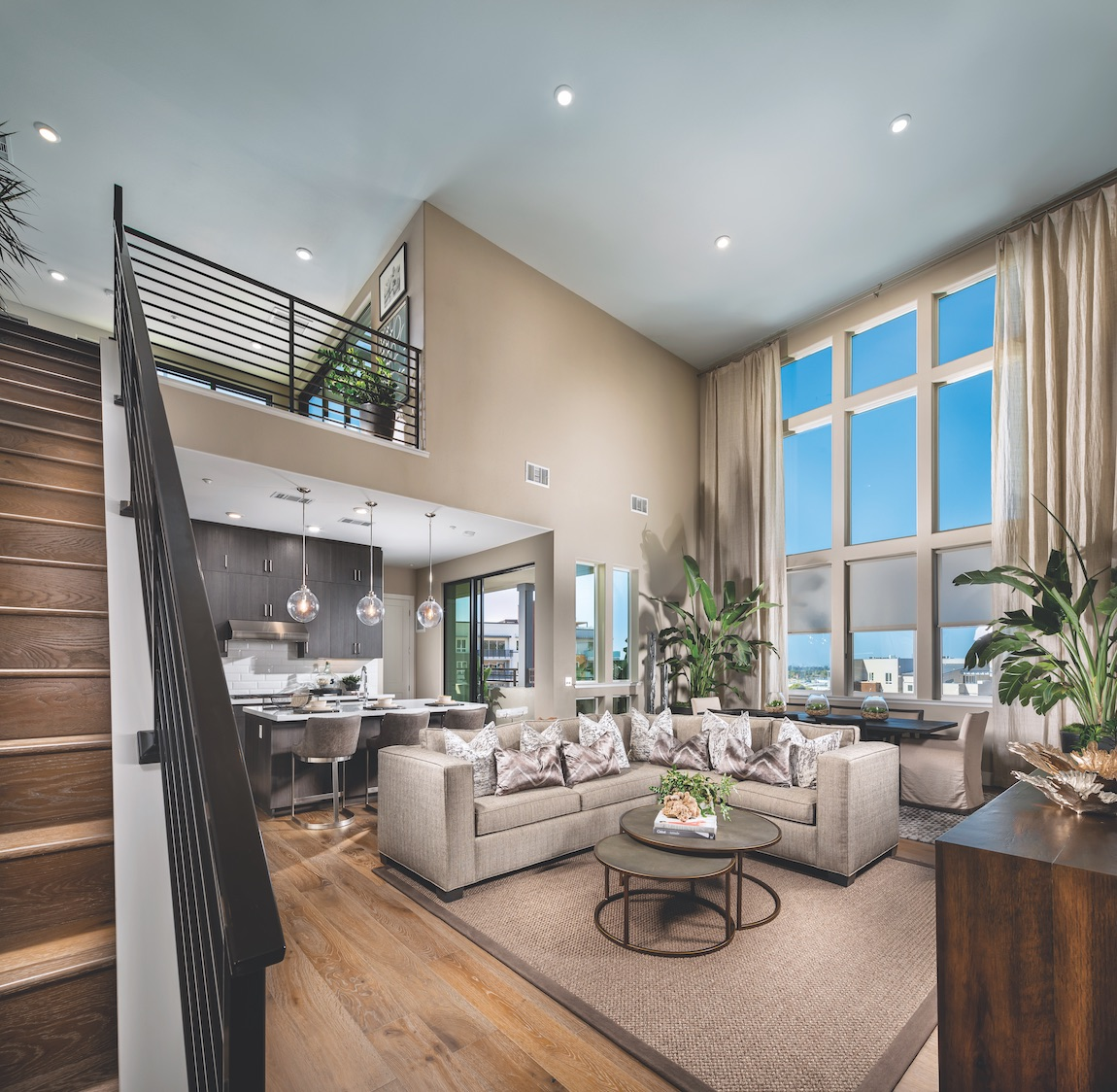 Interior of Metro Crossing home design with floor to ceiling windows, natural light, high hats and tan painted walls.