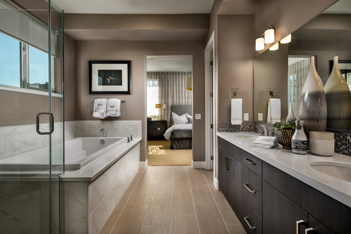 Bathroom with metal finishes, brown painted walls, square bathtub and quartz countertop.