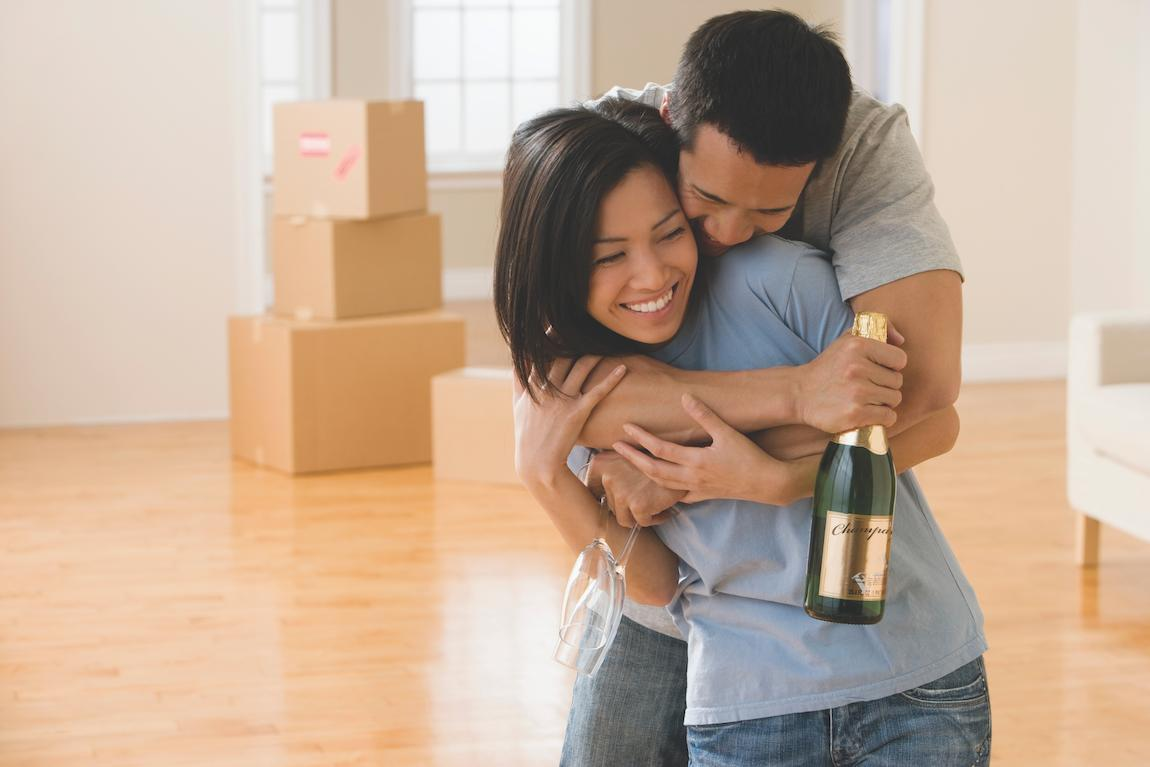 Couple celebrating the completion of cleaning their old home as a part of their moving checklist