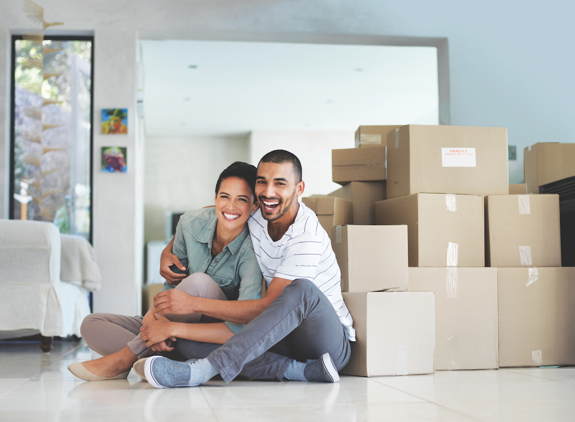Couple in front of packed boxes moving into new home