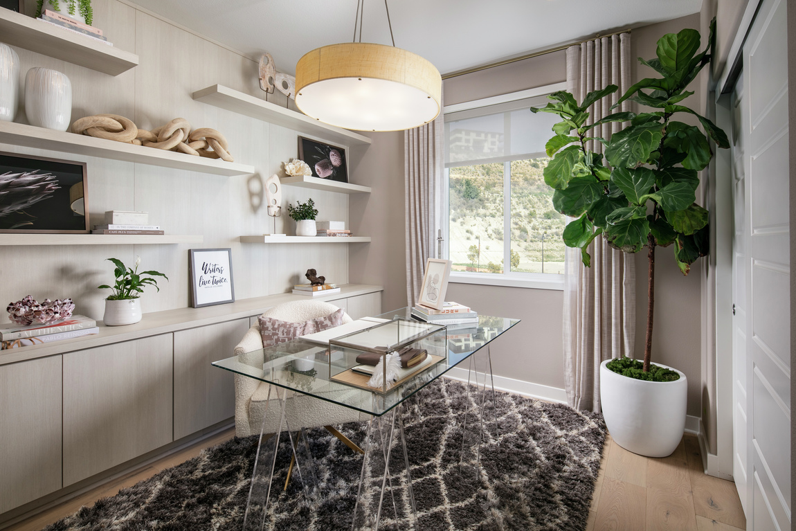 Office highlighted by glass desk and lighting fixture