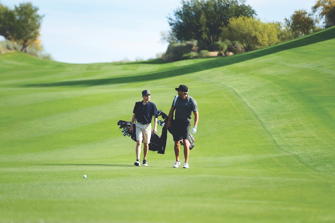 Two men walking on a golf course with golf clubs on a sunny day