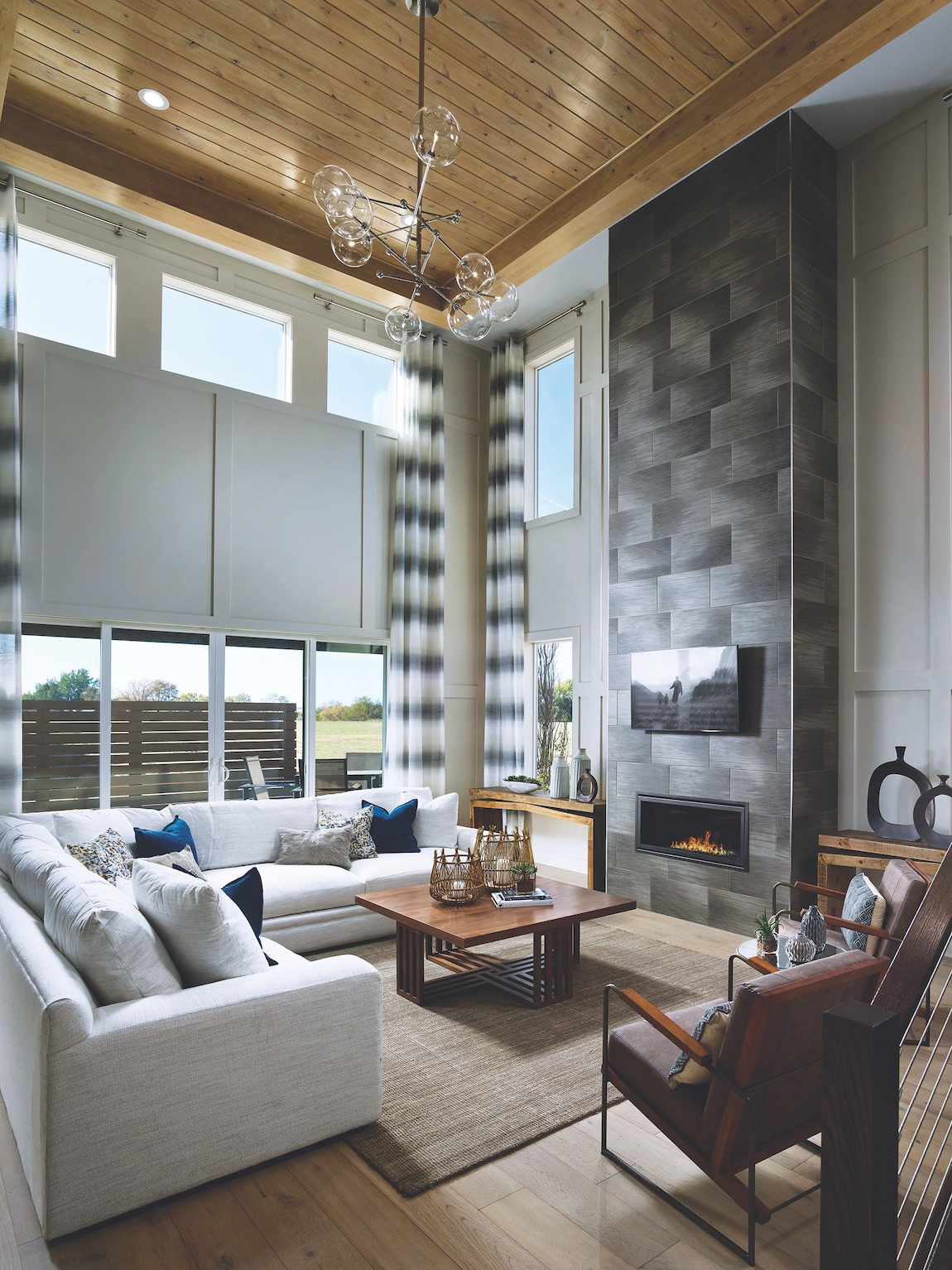 Great room with floor to ceiling windows, white couch, and electric fireplace
