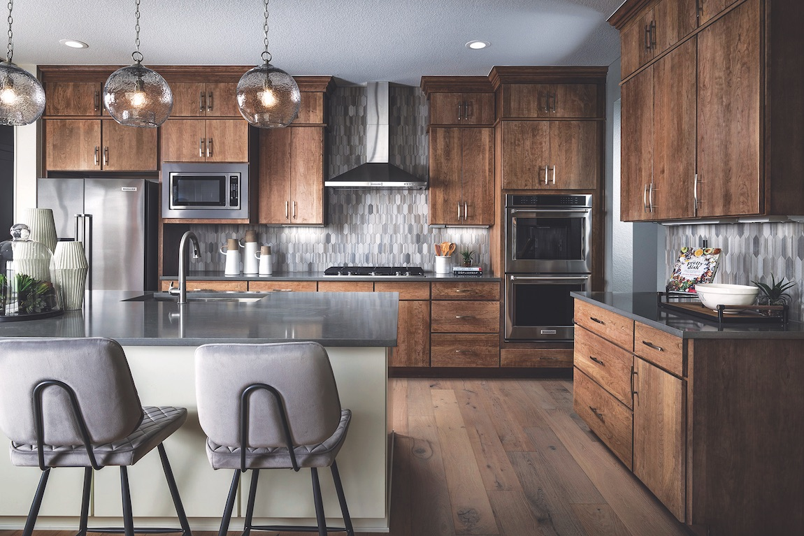 Kitchen with dark wood cabinets, quartz countertops and stainless steel appliances