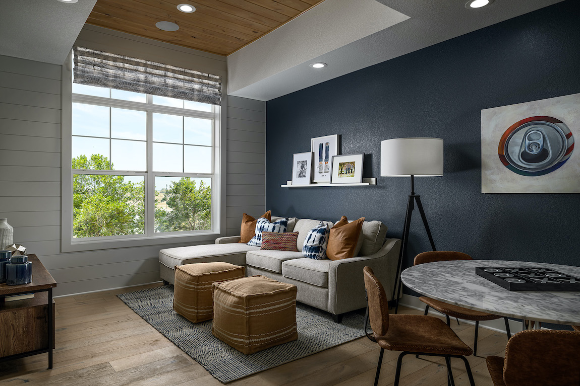 Loft with blue accent wall, game table and wall art