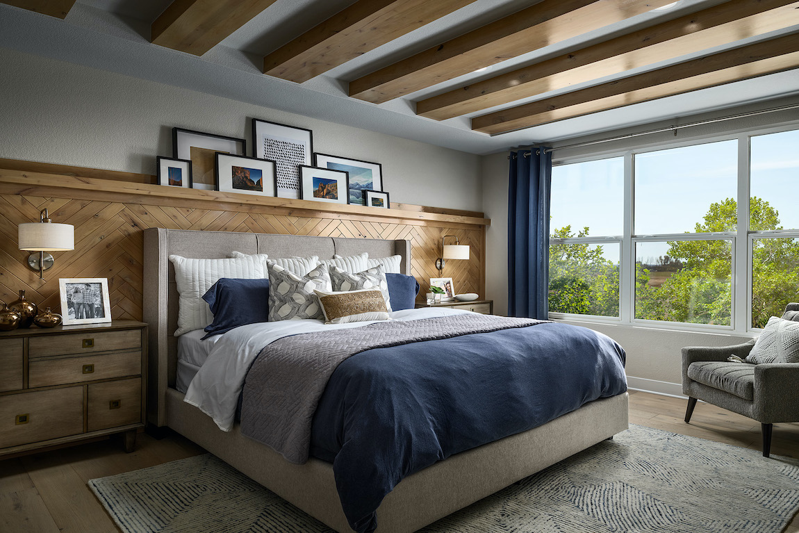 Bedroom with wooden beams, wood wall detail and blue comforter