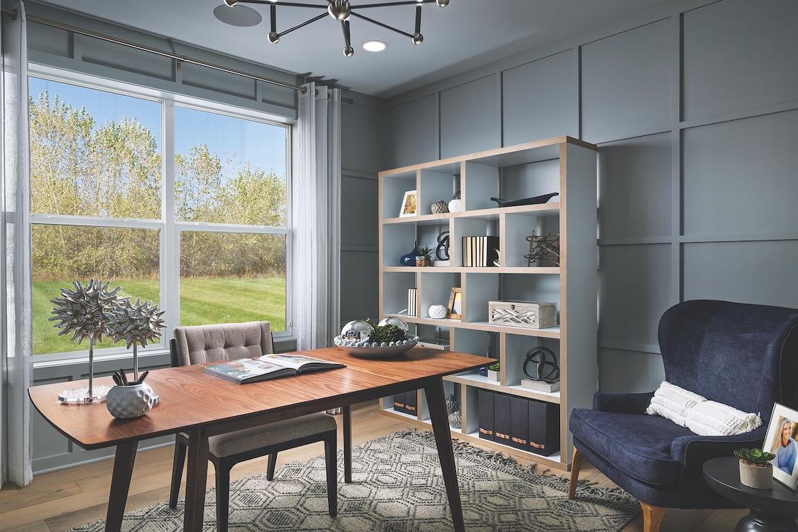 Office with bookshelf, wooden modern desk and blue armchair