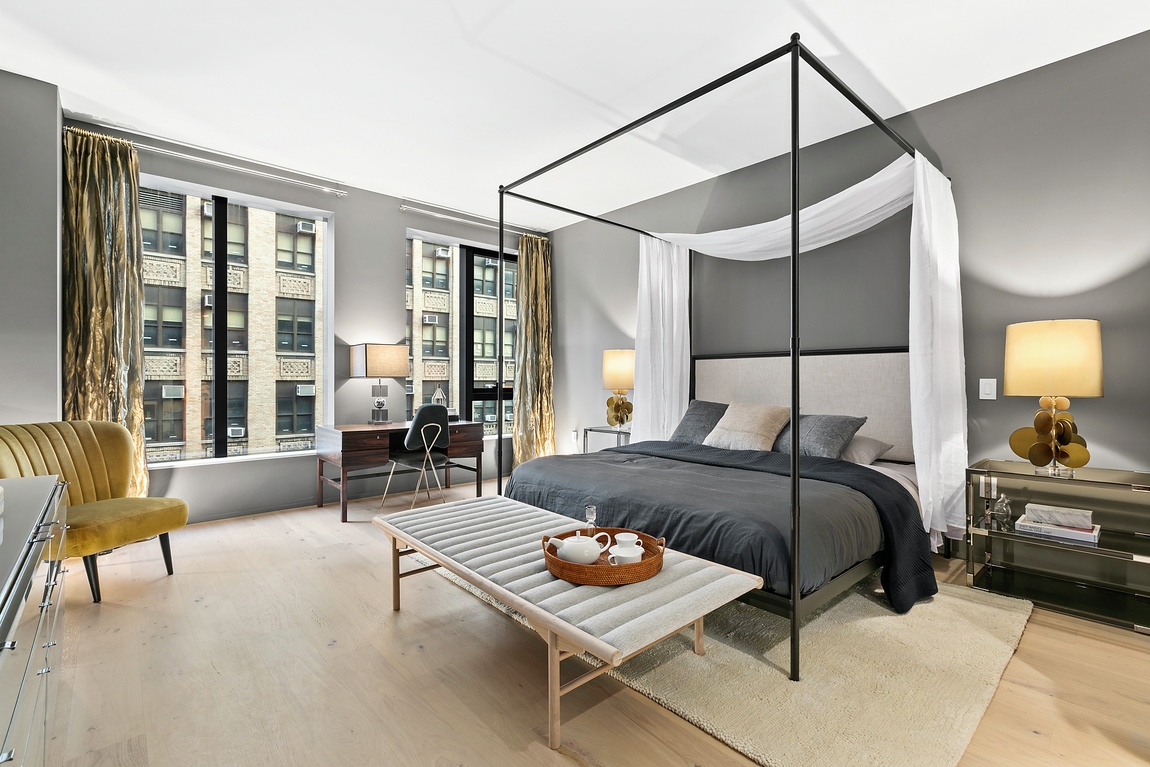 Grey bedroom with four poster bed, modern chairs and light wood flooring.