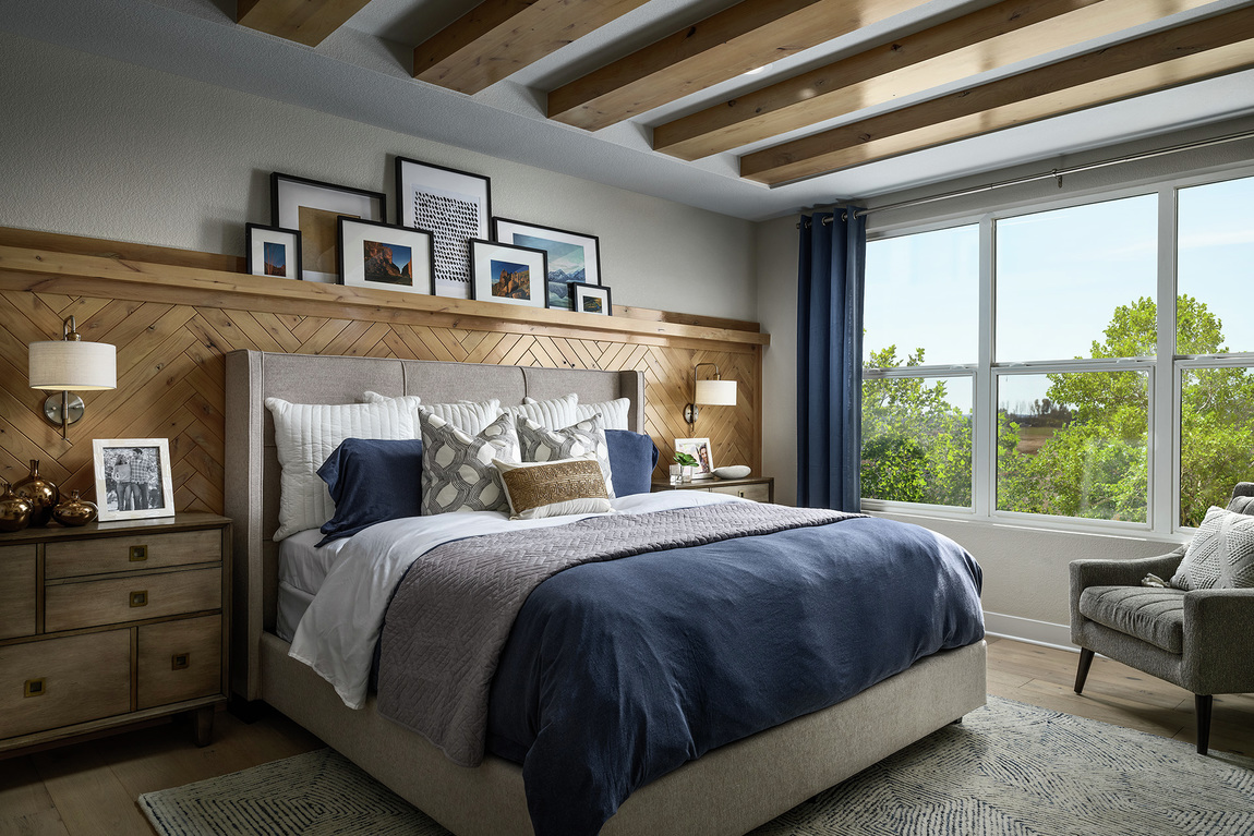Bedroom with grey paint, bed backboard, wood paneling and ceiling beams.