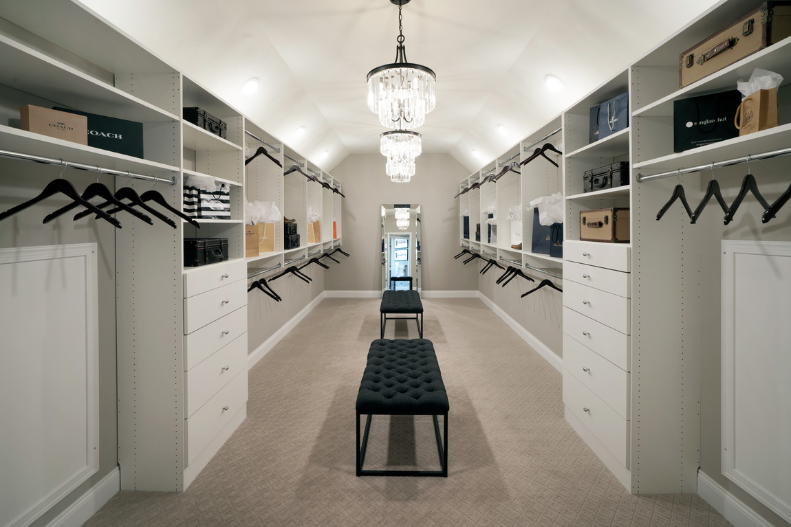 Dual closet with white cabinets and large space for hanging clothes