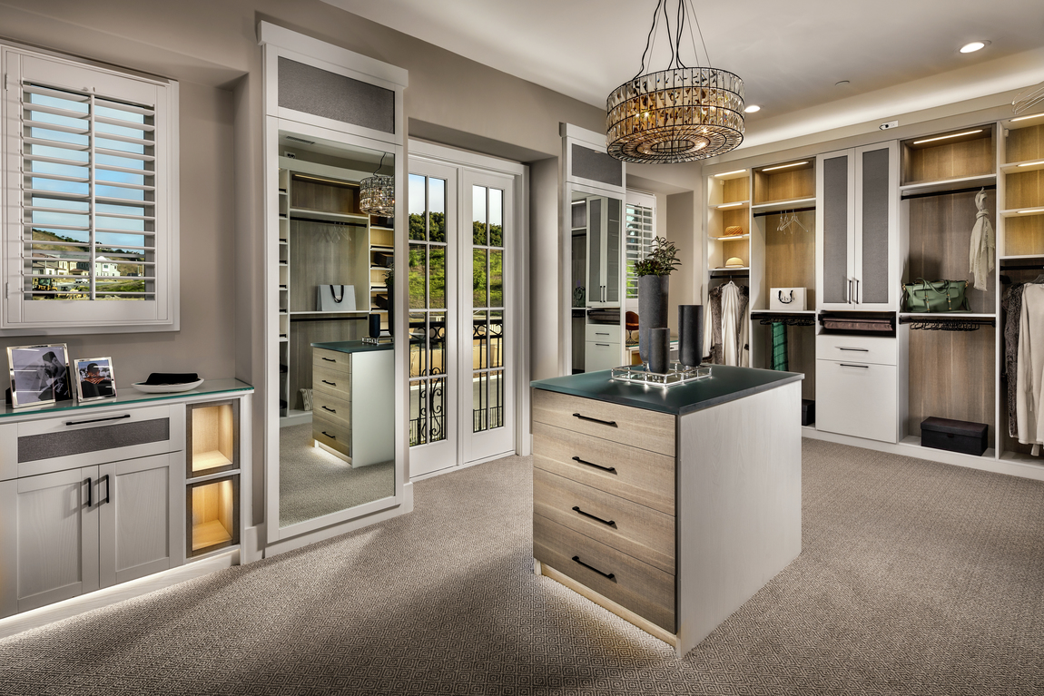Luxury closet with balcony, center island, jewelry space, floor to ceiling mirror, chandelier, and accent spotlighting