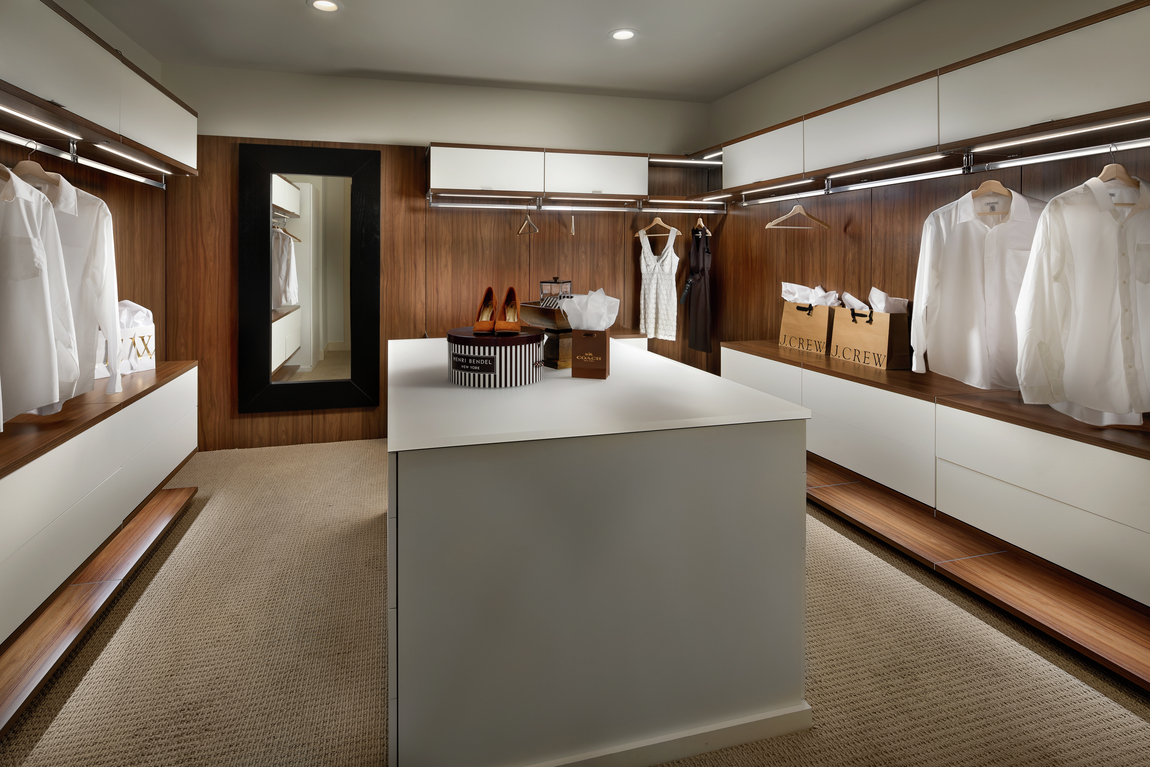 Modern closet with white center island and carpeting with plenty of hanging space.