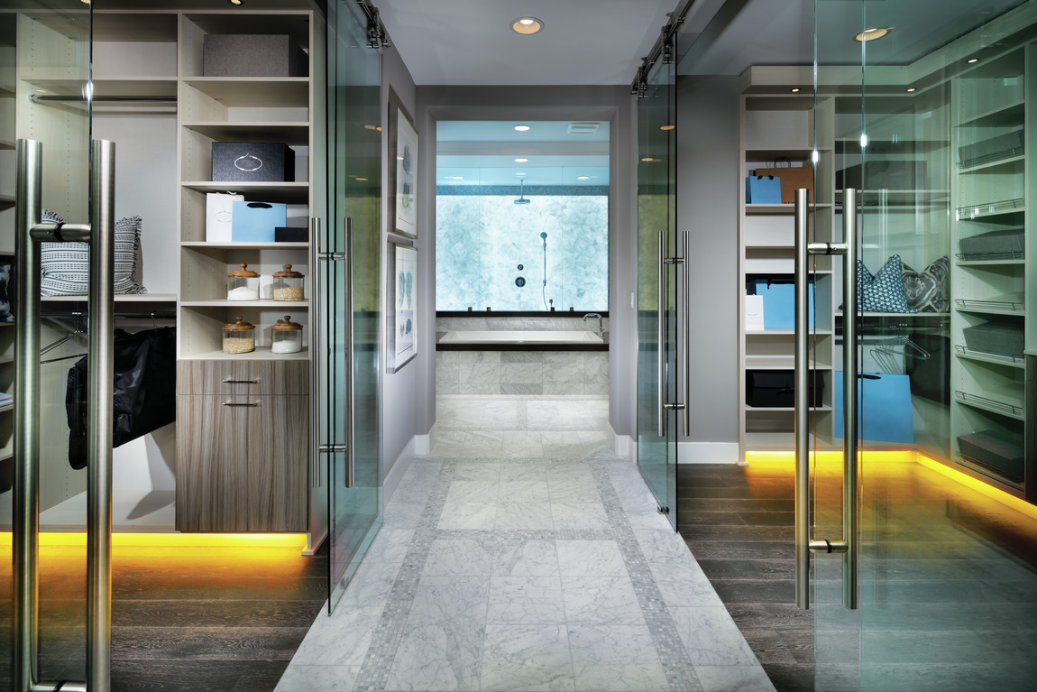 Clear glass closet doors with accent toe-kick lighting and wooden modern flooring