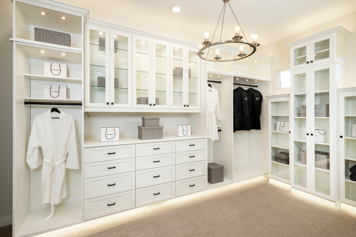 White closet cabinets with toe-kick lighting, spotlights, chandelier and glass cabinet doors.