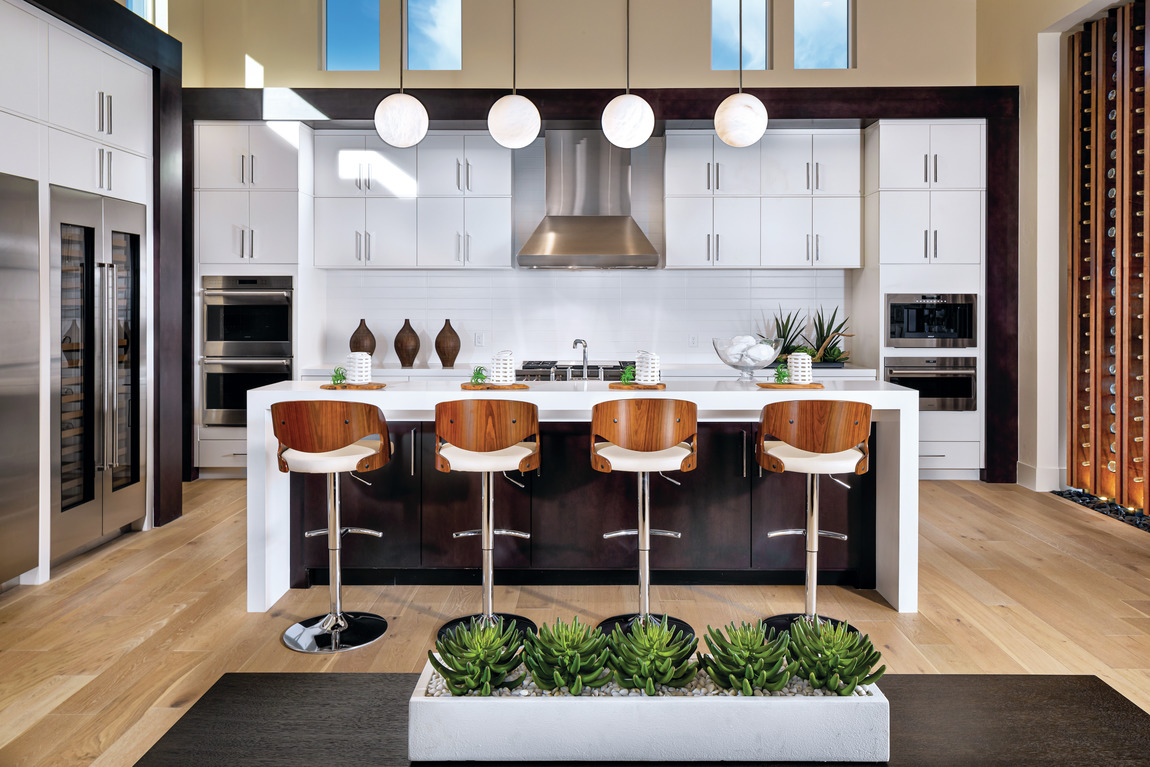 contemporary kitchen featuring waterfall island, pendant lighting, and innovative cabinetry