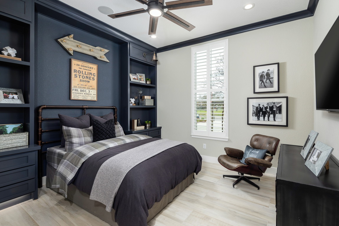 Bedroom with blue accent wall and built-ins with 5 blade ceiling fan