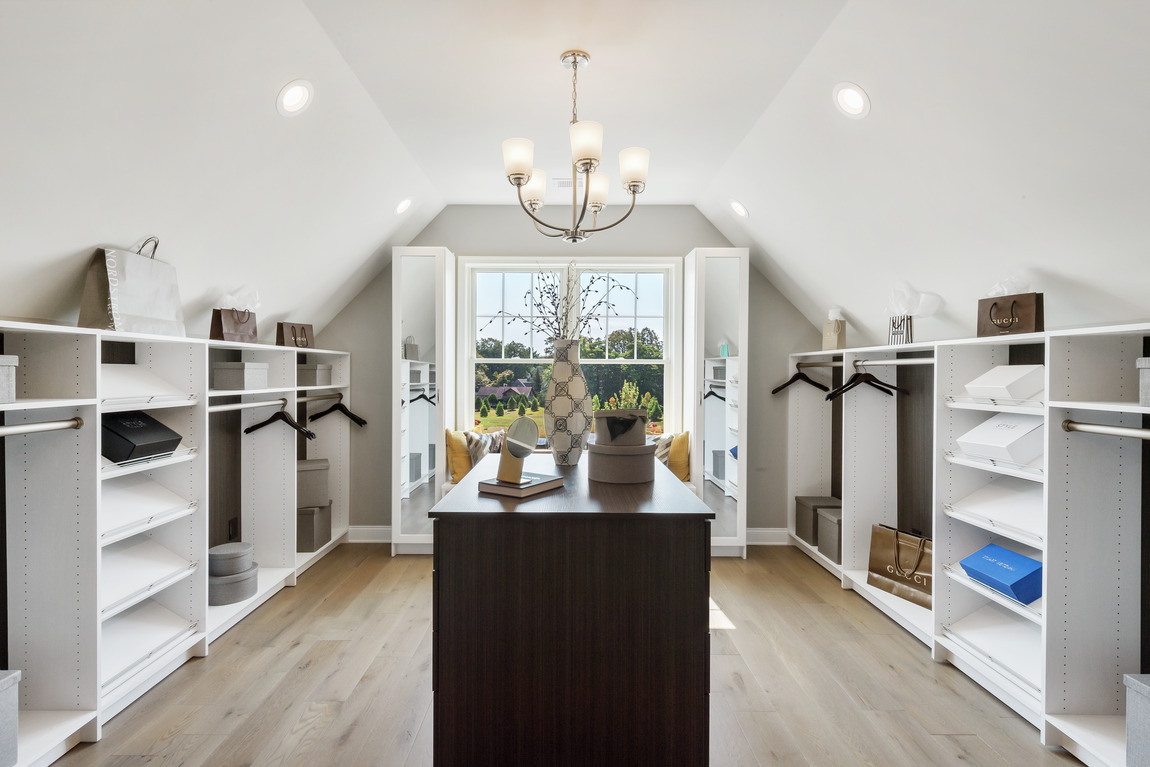 Closet in attic space with arched ceiling and natural lighting